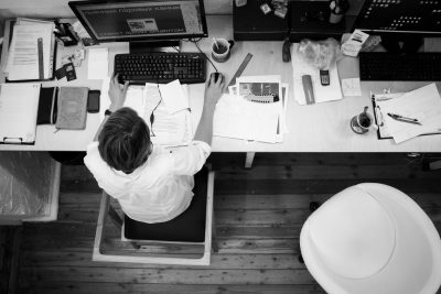 guy working at messy desk trying to write