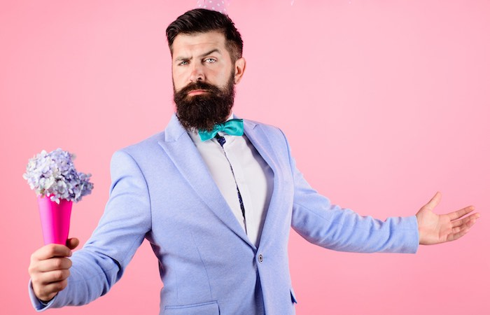 Gentleman in purple suit with blue bow tie and beard with flowers and pink background
